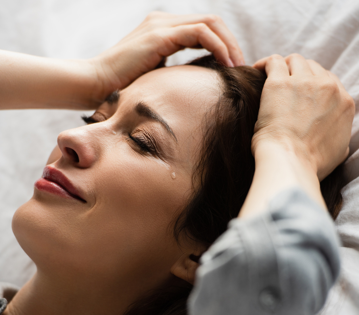 frustrated and brunette woman with closed eyes touching hair while crying on bed
